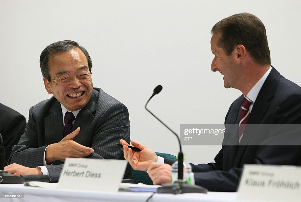Japanese auto giant Toyota Motor vice chairman Takeshi Uchiyamada (L) shares a light moment with German auto giant BMW board member Herbert Diess (R) at a press conference in Nagoya, central Japan on January 24, 2013 as they agreed several strategies including the possible joint development of a mid-sized sports vehicle. Toyota and BMW said they were deepening ties on developing fuel-cell technology and vehicle batteries as the auto giants push into the green market