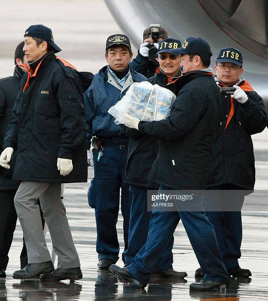 A Japanese aviation expert carries a battery, which leaked electrolyte, out of a All Nippon Airways (ANA) Boeing 787 Dreamlier plane at Takamatsu airport in Kagawa prefecture on Japan's western island of Shikoku on Janaury 17, 2013 after the plane made an emergency landing at the airport the day before after smoke was reportedly seen inside the cockpit. All Boeing Dreamliners operating in Japan must remain grounded until their batteries are confirmed to be safe, the government said on January 17, following a similar order in the US.