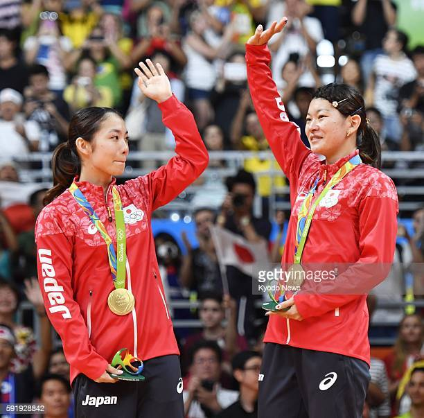 Japanese badminton pair Misaki Matsutomo and Ayaka Takahashi wave to the crowd during the award ceremony for the women's doubles event at the Rio de...