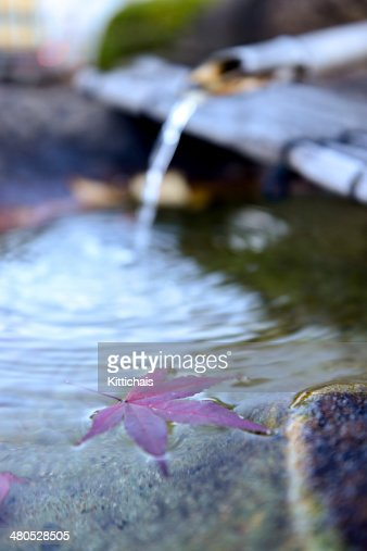Japanese Bamboo fountain with Autumn Red Maple Leaf. : Stockfoto