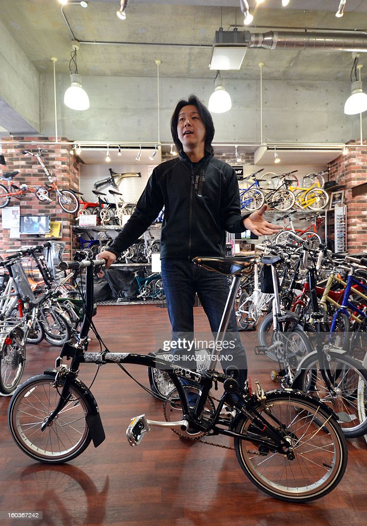 Japanese bicycle shop manager Seiji Hirata displays a Brompton folding bicycle at his shop 'Green Cycle Station' in Yokohama, in Japan, on January 27, 2013. British bicycle company Brompton produced 36,000 bikes in 2012 with a turnover of around GBP 20m (approx 23.25m euros). Brompton's folding bikes have proved popular with customers in Asian countries such as Japan. AFP PHOTO / Yoshikazu TSUNO