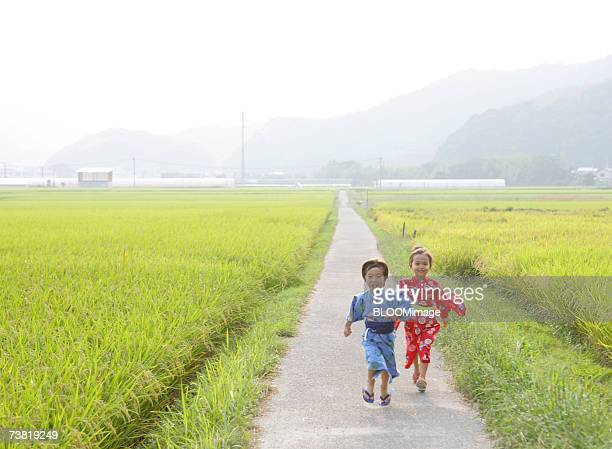 Japanese boy and girl wearing yukata running on country road