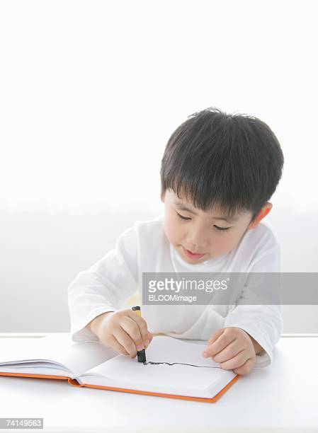 Japanese boy drawing picture with crayons