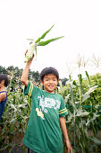 Japanese boy holding corn in the air
