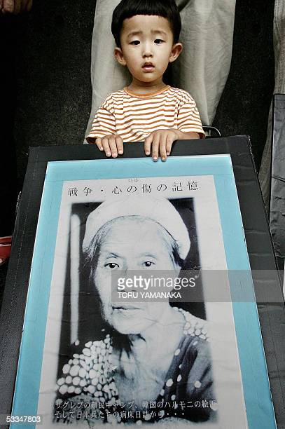 Japanese boy holds a portrait of late comfort woman Kang DokKyong of South Korea during a demonstration in front of the national parliament in Tokyo...