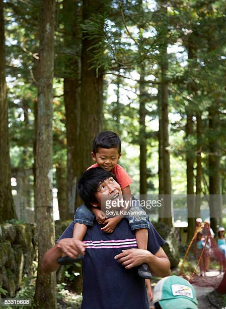 Japonés boy on his father's hombros; Sonriendo