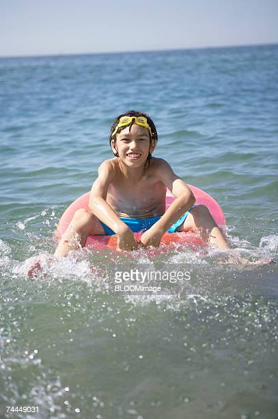 Japanese boy on swimming ring  with smiling in the sea