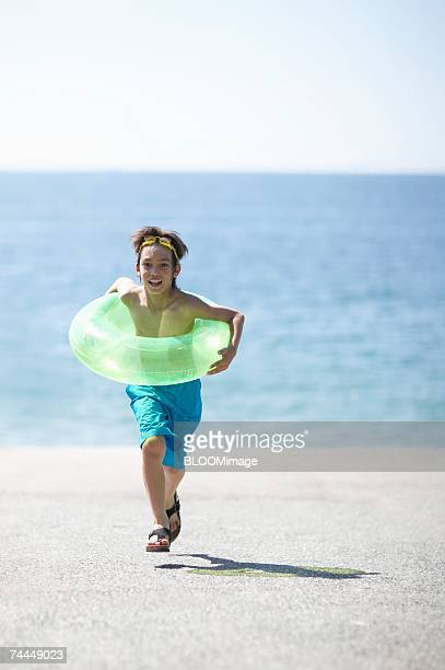 Japanese boy running with holding swimming ring