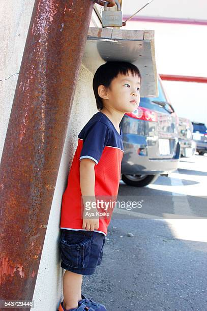 A Japanese boy trying to calculate his height in a parking area