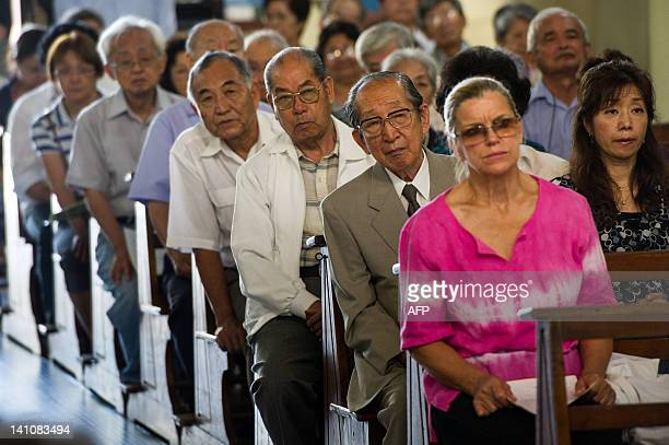 Japanese Brazilians attend a mass on the day before of the first anniversary of the earthquaketsunami disaster in Japan at Sao Goncalo Church in Sao...