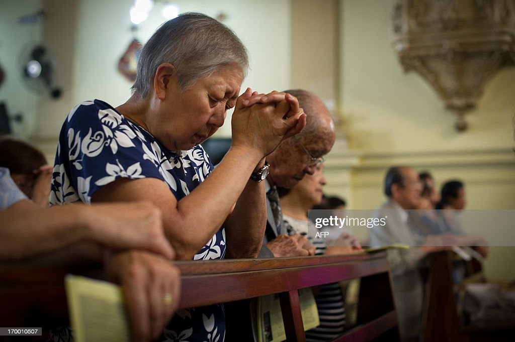 Japanese Brazilians pray on the day before of the first anniversary of the earthquake-tsunami disaster in Japan at Sao Goncalo Church in Sao Paulo, Brazil on March 10, 2012. The church locates next to Liberdade area where many Japanese immigrants and descendants live. The disaster happened in the Northeast of Japan and left more than 19,000 people dead or missing. AFP PHOTO/Yasuyoshi Chiba