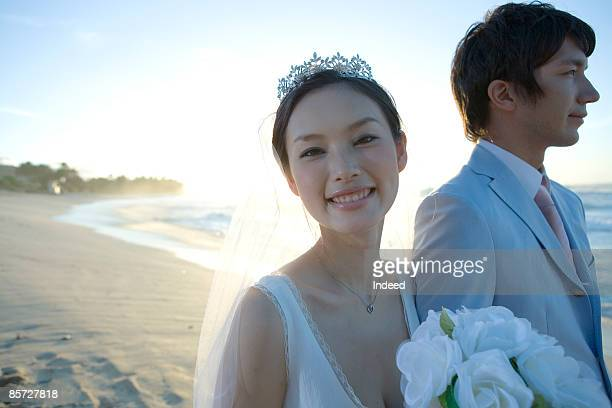 Japanese bride smiling with groom on beach