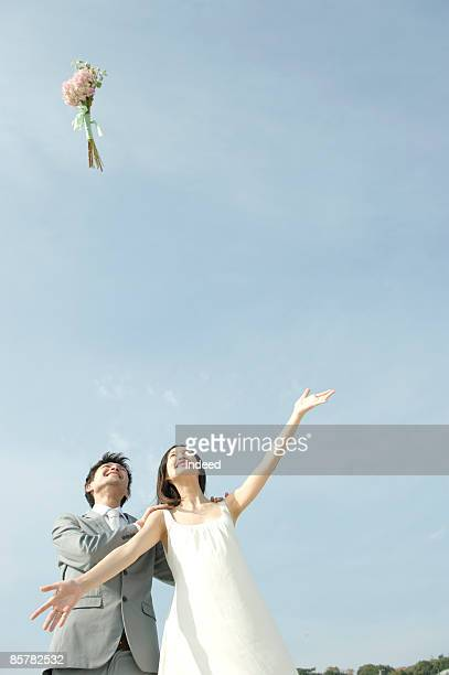 Japanese bride throwing bouquet with groom