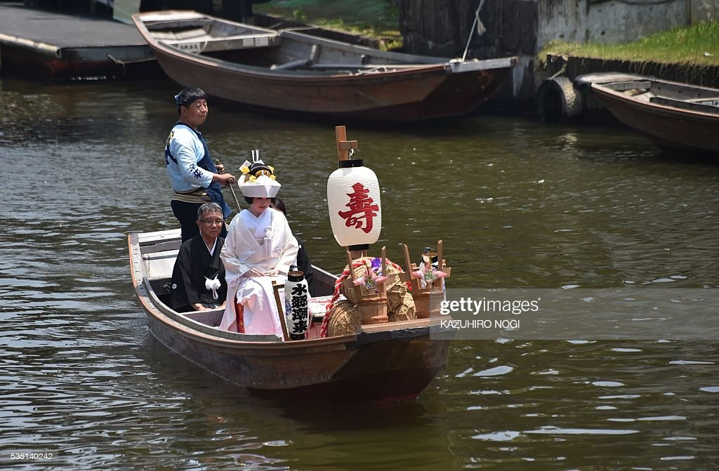 A Japanese bride wearing a pure white kimono rides a boat with her parents for her wedding in Itako city, some 80 kilometres northeast of Tokyo, May 29, 2016, as part of the annual Ayame (iris) flower festival. Yomeiri-fune (a boat escorting a bride) and local Japanese entertainment is performed during the festival period. / AFP / KAZUHIRO
