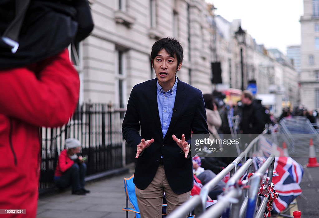 A Japanese broadcast journalist reports opposite St James's Palace in central London on October 23, 2013, where Prince George of Cambridge will be baptised later in the day inside Chapel Royal. Prince William and his wife Catherine gather close friends and family for the christening of their baby son Prince George, in a low-key ceremony far removed from the global hype surrounding their wedding.