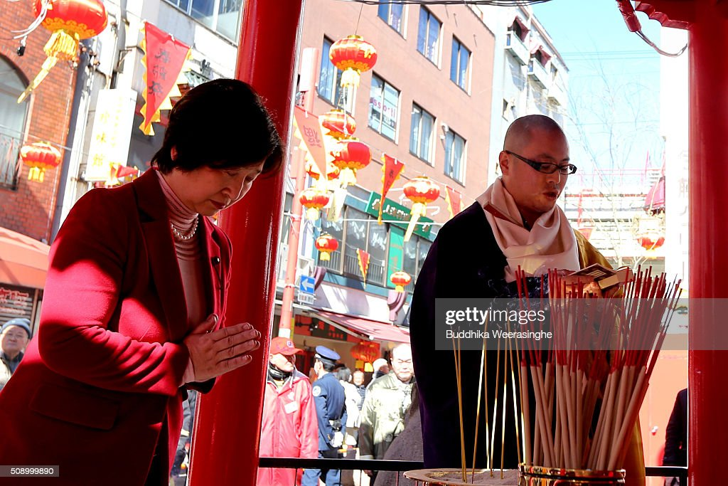 A Japanese Buddhist monk performs religious ritual to celebrate the Chinese New Year as a woman prays at the Nankinmachi square, China Town on February 8, 2016 in Kobe, Japan. In Nankinmachi, the district known as Kobe Chinatown, tourists enjoyed Chinese food, lion dance and the parade organized to celebrate the Lunar New Year.