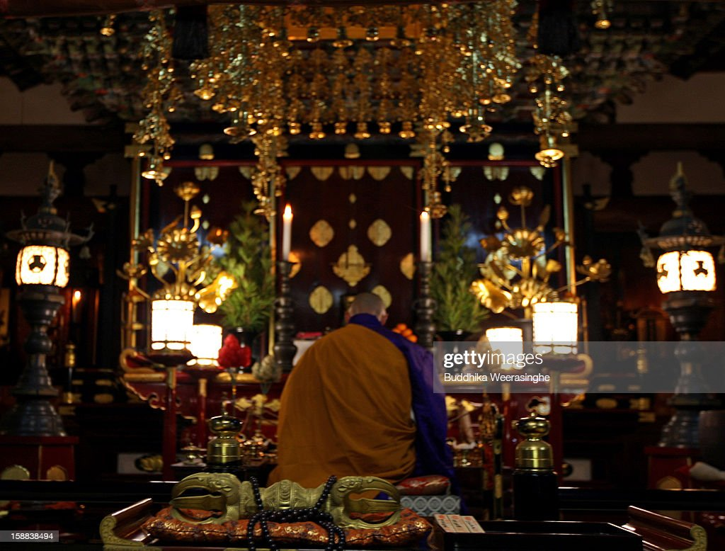 A Japanese Buddhist monk prays at the Sagami-ji Buddhist temple on January 1, 2013 in Kasai, Japan. Japanese people attend the Buddhist temple at midnight on December 31 for the ringing of the temple bell to welcome in the New Year or 'Omisoka' as it is known in Japan. In Japanese belief there are 108 elements to the human mind, so the bell is rung 108 times as a blessing of happiness for the New Year.