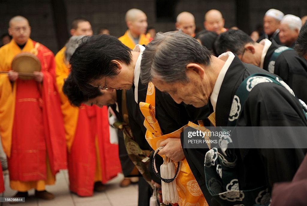 Japanese Buddhist monks bow and pray for Nanjing massacre victims on the 75th anniversary of the Nanjing massacre at the Memorial Museum in Nanjing on December 13, 2012. Air raid sirens sounded in the Chinese city of Nanjing on December 13 as it marked the 75th anniversary of the mass killing and rape committed there by Japanese soldiers -- with the Asian powers' ties at a deep low. AFP PHOTO/Peter PARKS