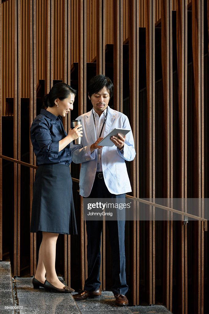 Japanese business colleagues with tablet outside modern office building