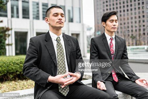 Japanische Business Mann tun yoga zusammen auf die Innenstadt