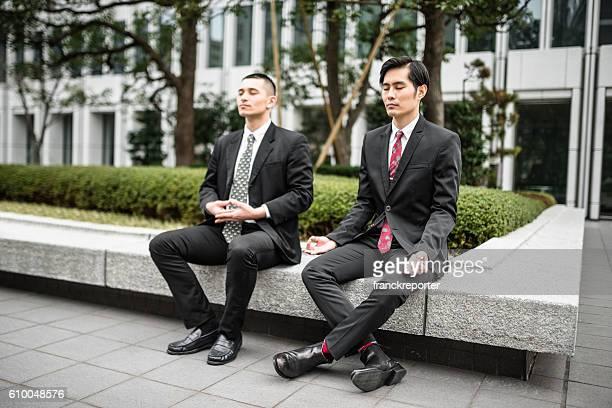 Hombre de negocios japonés haciendo yoga juntos en el centro de la ciudad
