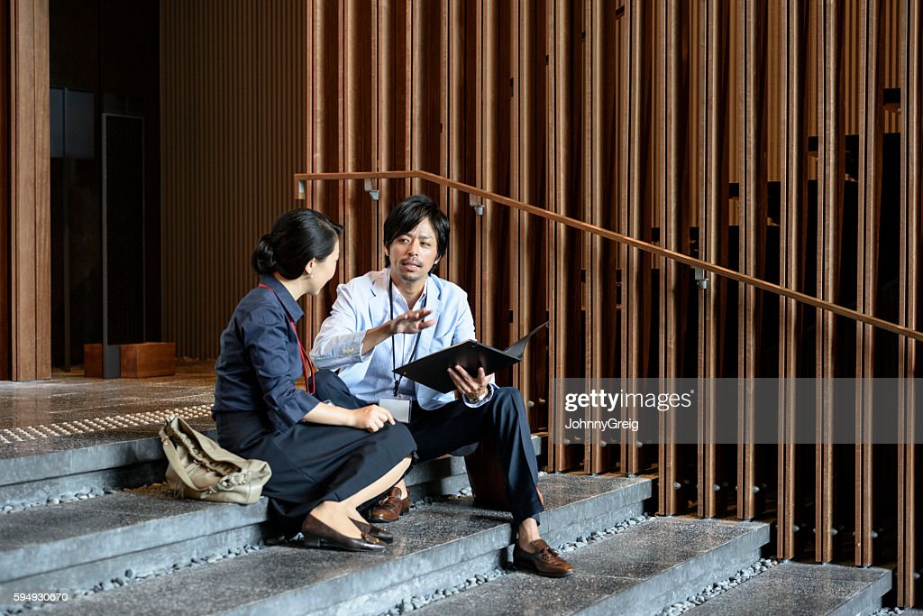 Japanese business people sitting on steps discussing