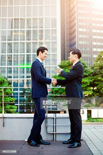Japanese business people warmly greating.
