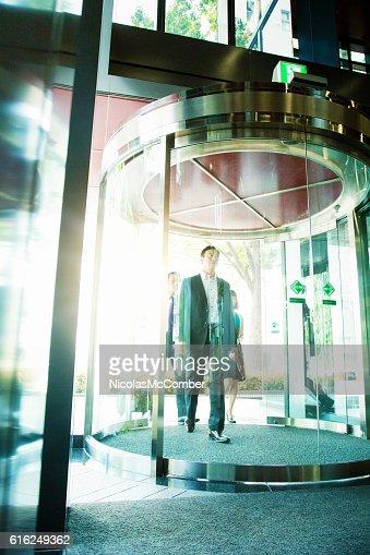 Japanese business team walking through revolving doors : Foto de stock