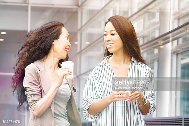 Japanese business woman laughs with assistant on coffee break