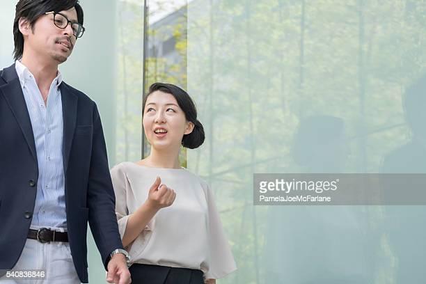 日本実業家と女性実業家話す、徒歩でモダンなオフィスビル
