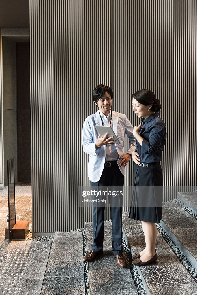 Japanese businessman and woman outside building with tablet
