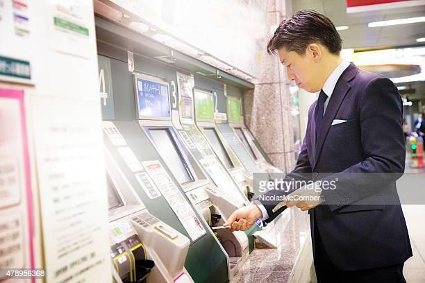 Japanese businessman buying Tokyo subway ticket at automatic teller