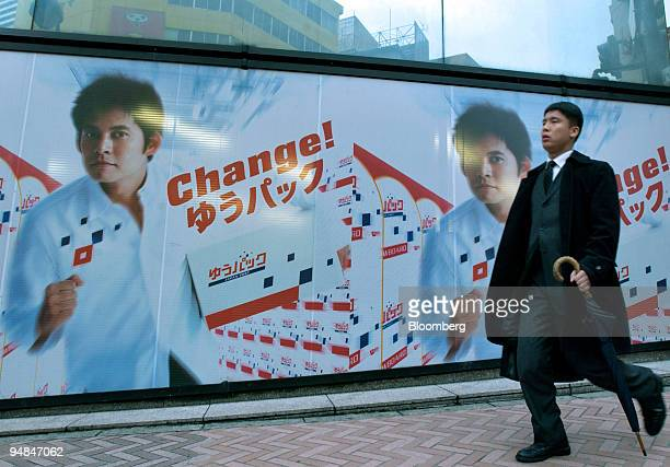 Japanese businessman carrying an umbrella walks by a Tokyo post office decorated with an advertisement for its package delivery service featuring the...