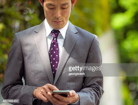 Japanese businessman concentrating on smart phone message