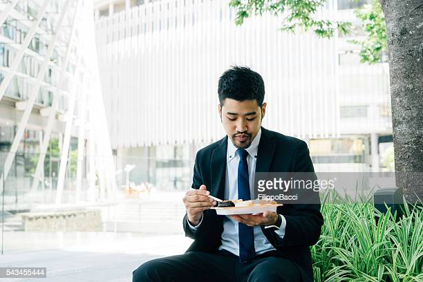 Japanese Businessman Eating Sushi