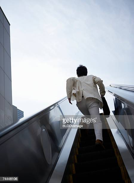 Japanese businessman going up escalator