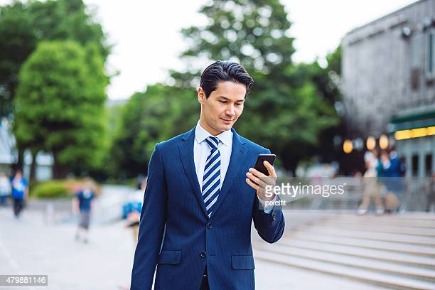 Japanese businessman in Tokyo with smart phone texting outdoors