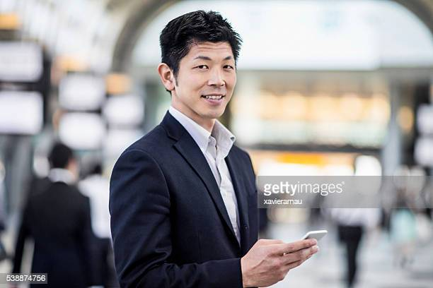 Japanese businessman portrait looking at his phone at the station