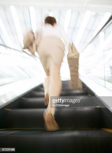 Japanese businessman running up escalator