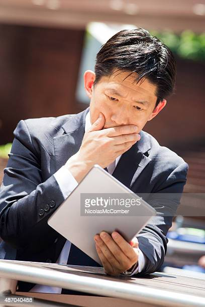 Japanese businessman stricken with grief guilt fear looking at tablet