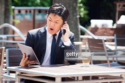Japanese businessman swears on mobile phone while looking at tablet : Stock Photo