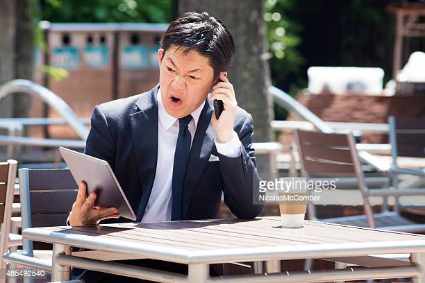Japanese businessman swears on mobile phone while looking at tablet