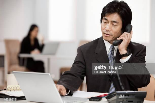 日本のビジネスマンのデスク電話で話している