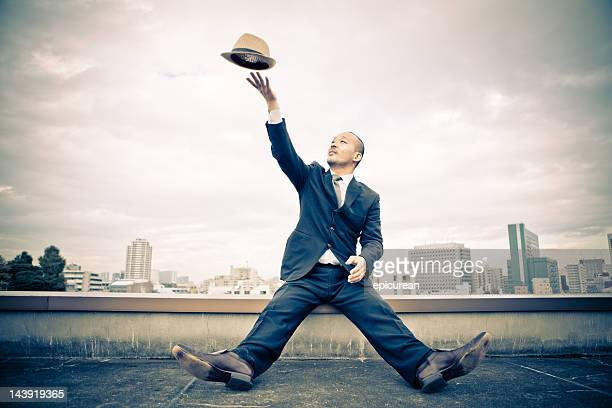 Japanese businessman tossing his hat in the air