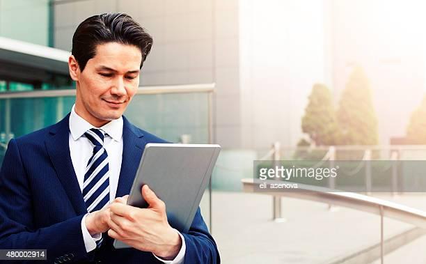Japanese businessman using digital tablet, Tokyo.