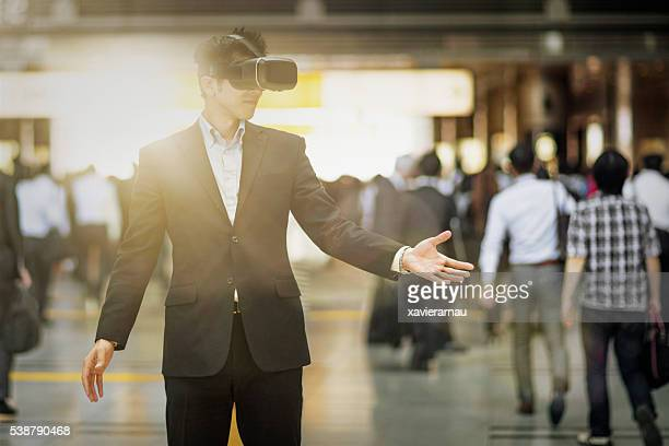 Japanese businessman using VR glasses in the street