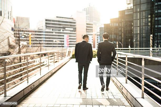 japanese businessman walking and talking on the city