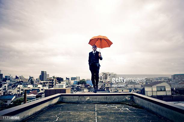 Japanese businessman with umbrella floating above Tokyo