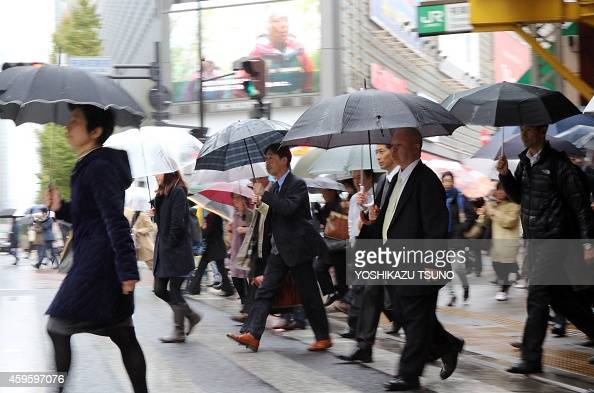 Japanese businessmen and women cross the road in Tokyo on November 26 2014 Japan's economy shrank between July and September the second consecutive...