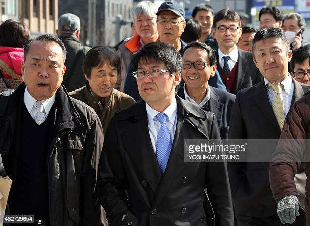 Japanese businessmen cross a road in Tokyo on February 4 2015 Japan is considering making it compulsory for workers to take at least five days' paid...